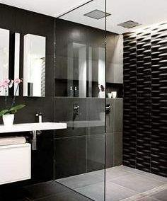 black tiled bathroom with walk in shower with black frameless shower panel